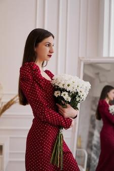 Piękna brunetka w czerwonej sukience z bukietem stokrotek w domu
