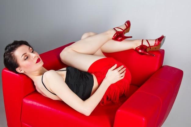 Piękna brunetka w czerwonych butach siedzi w czerwonym fotelu na szarym tle.