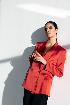 Piękna brunetka w czerwonym płaszczu i w czarnych spodniach marynarce garniturze w modnym stylu