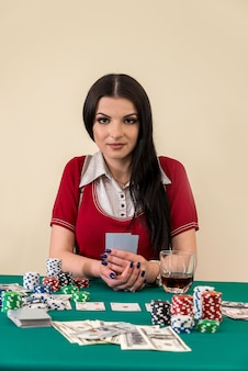 Piękna brunetka w kasynie trzymając karty do gry