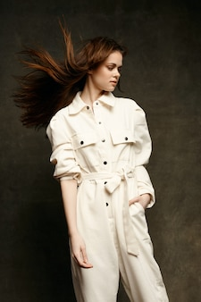 Piękna brunetka w lekkim kombinezonie na ciemnym tle trzyma ręce w kieszeni. wysokiej jakości zdjęcie