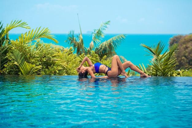 Piękna brunetka w niebieskim stroju kąpielowym odpoczywa na brzegu basenu bez krawędzi. letni wypoczynek. tropikalna przyjemność