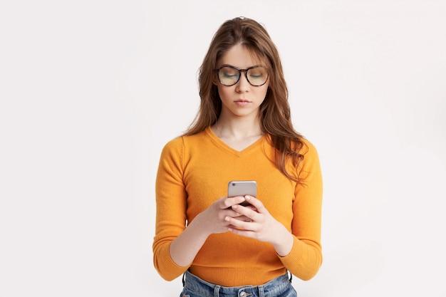 Piękna brunetka w okularach i żółty sweter odpowiada na wiadomości w swoim telefonie