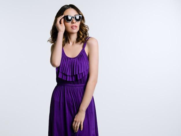 Piękna brunetka w okularach przeciwsłonecznych i purpurowej sukience
