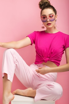 Piękna brunetka w studio na różowym tle