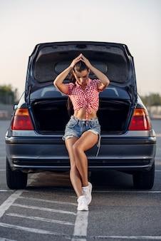 Piękna brunetka w szortach i czerwonej koszuli oparła się na bagażniku swojego samochodu.