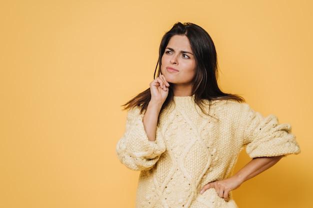 Piękna brunetka w żółtym swetrze, patrząc w zamyśleniu na wolną przestrzeń. ciekawe, aby to wybrać.