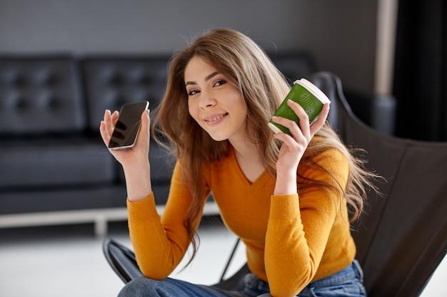 Piękna brunetka w żółtym swetrze siedzi na stylowym krześle z czarnej skóry, trzyma w dłoni filiżankę kawy i telefon. praca, komunikacja w domu, biuro