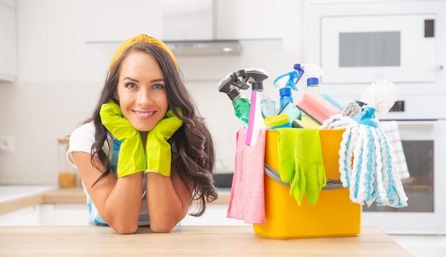 Piękna brunetka woźna opierając się na łokciach, uśmiechając się do kamery, obok niej znajdują się środki dezynfekujące.