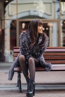 Piękna brunetka z długimi prostymi włosami ubrana w szary futro, białą koszulę i czarną spódnicę siedzącą na ławce i uśmiechająca się