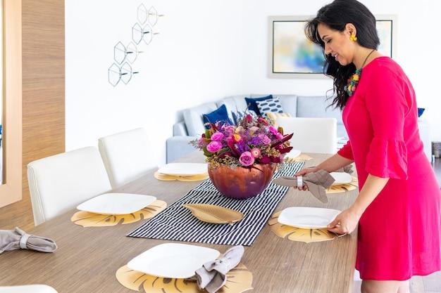 Piękna brunetka z długimi włosami i czerwoną sukienką dekoruje stół kompozycją kwiatową wewnątrz kolorowej pomalowanej dyni, aby uczcić inne halloween