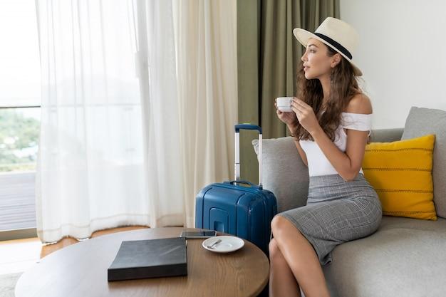 Piękna brunetka z kręconymi włosami siedzi na kanapie w lekkim kapeluszu i pozuje z walizką i filiżanką kawy, patrząc przez okno