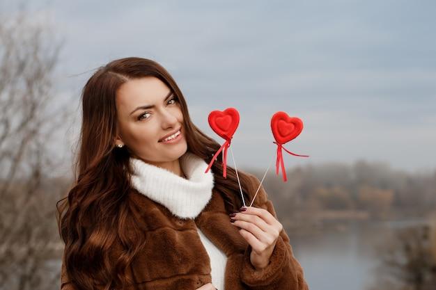 Piękna brunetka z sercami w rękach