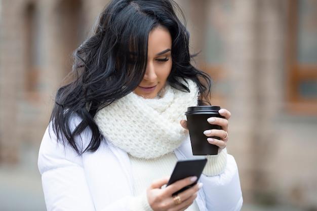 Piękna brunetka ze smartfonem i kawą na ulicy europejskiego miasta w sezonie zimowym