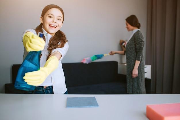 Piękna brunetki caucasian matka i córka czyści wpólnie w pokoju. ładna, zabawna dziewczyna wygląda na caera i używa na niej psray. ona gra. jej mama rozwala kurz.