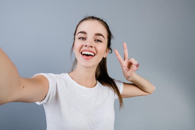 Piękna brunetki dziewczyna jest ubranym białą koszula robi selfie odizolowywającemu nad popielatym