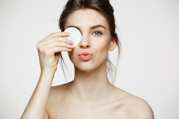 Piękna brunetki dziewczyna ono uśmiecha się z czystą perfect skórą chuje oko za bawełnianą gąbką ono uśmiecha się patrzejący kamerę nad białym tłem. kosmetologia i spa.