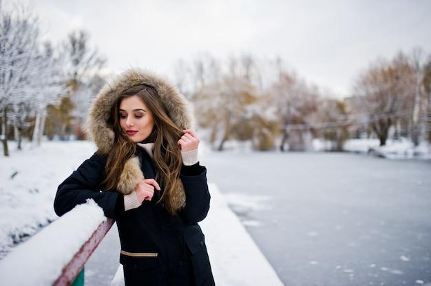 Piękna brunetki dziewczyna w zimy ciepłej odzieży. model na kurtce zimowej przeciwko zamarzniętemu jezioru w parku.
