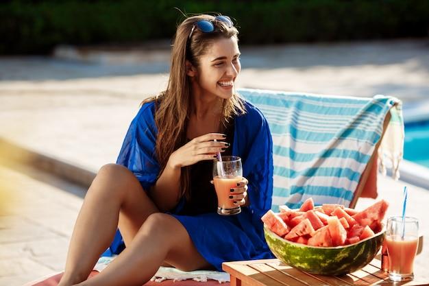 Piękna brunetki kobieta ono uśmiecha się, pije koktajl, siedzi blisko pływackiego basenu