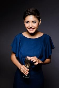 Piękna brunetki kobieta ono uśmiecha się w wieczór sukni, trzyma champaign szkło