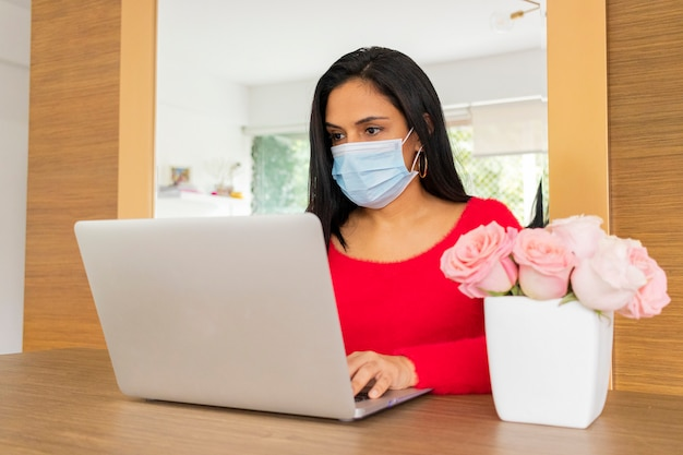 Piękna brunetki kobieta pracuje od domu z jej laptopem