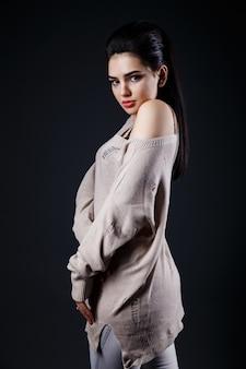 Piękna brunetki kobieta w beżowym pulowerze