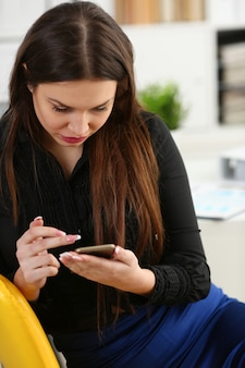 Piękna brunetki kobieta w biurowym chwyta telefonie przy miejscem pracy
