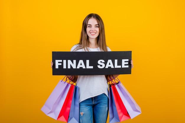 Piękna brunetki kobieta z kolorowymi torba na zakupy i copyspace teksta definitywnej sprzedaży znaka sztandarem odizolowywającym nad kolorem żółtym