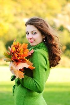 Piękna brunetki kobieta z liśćmi klonu