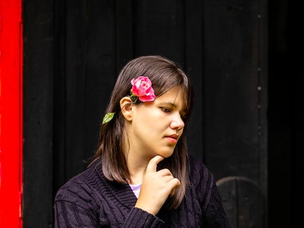 Piękna brunetki kobieta z różą na jej uchu i rękami na podbródku, myśląc o życiu w powierzchni piękne rustykalne czerwone okno