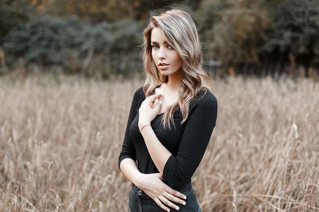 Piękna całkiem seksowna młoda kobieta w czarnej stylowej koszulce z blond włosami w modnych dżinsach pozuje na polu w ciepły jesienny dzień