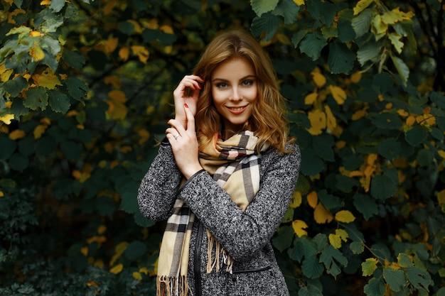 Piękna całkiem szczęśliwa młoda kobieta z uroczym uśmiechem w szaliku vintage w modnym szarym płaszczu pozuje w parku na tle żółto-zielonych liści