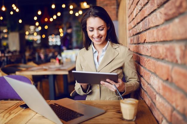 Piękna caucasian brunetka ubierał mądrze przypadkowego obsiadanie w kawiarni i używać pastylkę. na biurku jest laptop i kawa.