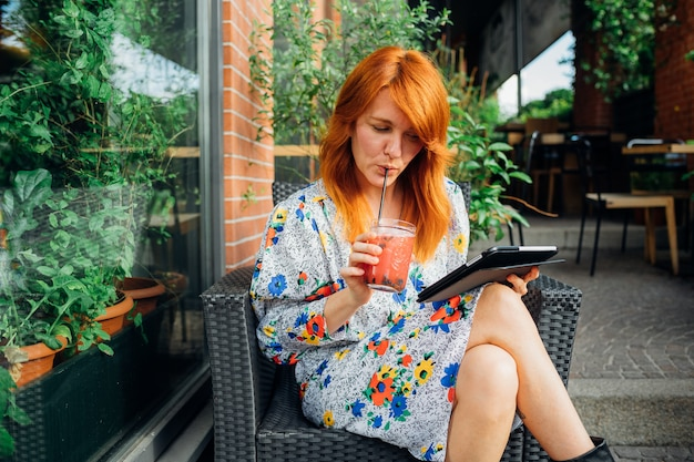 Piękna caucasian dorosła kobieta pije zdrowego smoothie