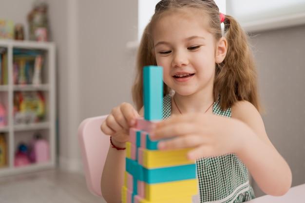 Piękna caucasian dziewczyna bawić się z drewnianymi wielobarwnymi blokami