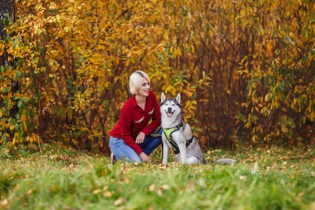 Piękna caucasian dziewczyna bawić się z husky psem w jesień lesie