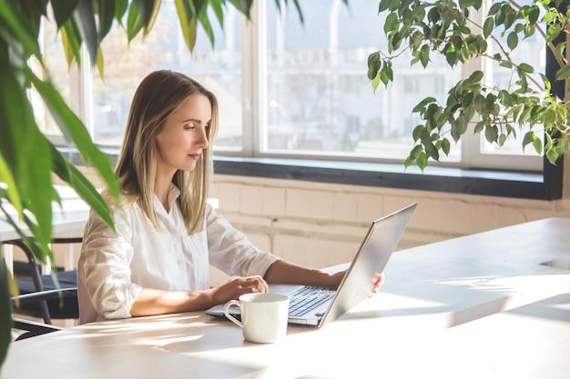 Piękna caucasian dziewczyna pracuje na laptopie zdalnie w jaskrawej przestrzeni z zielonymi roślinami.