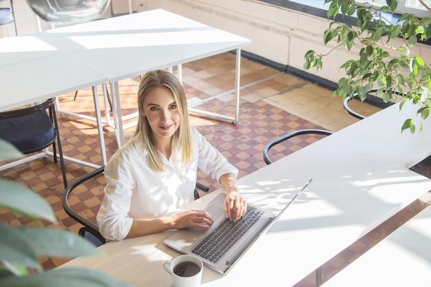 Piękna caucasian dziewczyna pracuje na laptopie zdalnie w jaskrawym wnętrzu.