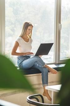 Piękna caucasian dziewczyna pracuje na laptopu obsiadaniu na parapecie w jaskrawym obszarze roboczym.
