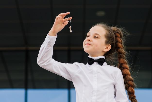 Piękna caucasian dziewczyna trzyma samochodowych klucze, mieszkanie. światowy dzień bez samochodu.