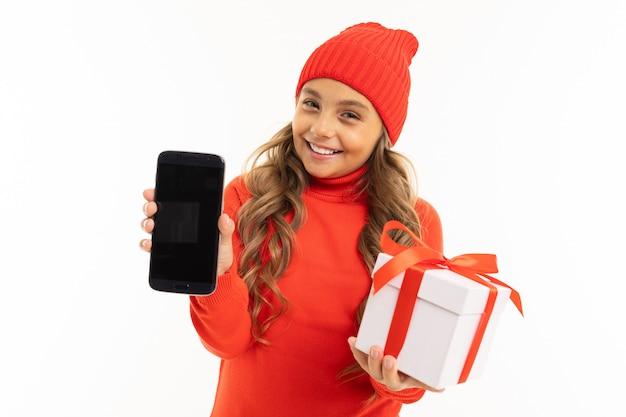 Piękna caucasian dziewczynka trzyma białe pudełko z prezentem w jednej ręce i smartfonem w drugiej ręce, uśmiecha się i wybiera między nim na białym