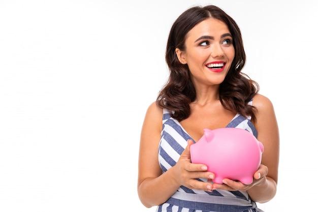 Piękna caucasian kobieta trzyma różowego świniowatego moneybox, obrazek odizolowywający na białym tle