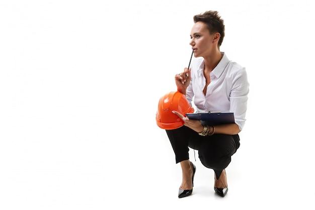 Piękna caucasian kobieta w biurowych ubraniach myśleć o pracie, pisze notatkach i trzyma pomarańczowego budowa hełm odizolowywającego na białym tle