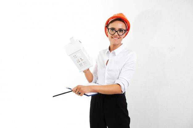 Piękna caucasian kobieta w biurowych ubraniach myśleć o pracie, pisze notatkach, ono uśmiecha się i trzyma pomarańczowego budowa hełm odizolowywającego na białym tle