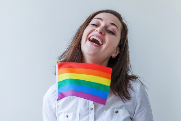 Piękna caucasian lesbijek dziewczyna z tęczową flagą lgbt na białym, patrząc szczęśliwy i podekscytowany. portret młodej kobiety gay pride. równe prawa do koncepcji społeczności lgbtq