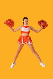 Piękna cheerleaderka na kolorowej powierzchni