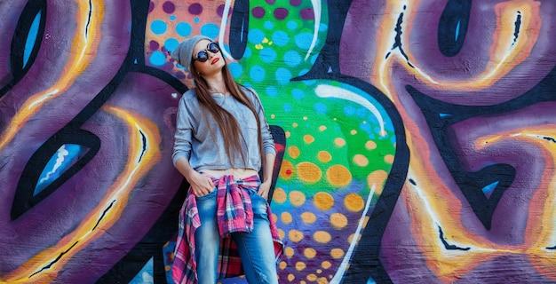 Piękna chłodno dziewczyna w kapeluszu i okularach przeciwsłonecznych nad graffiti ścianą