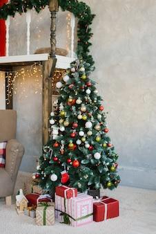 Piękna choinka z czerwonymi, białymi i złotymi kulkami i prezentami pod nią w salonie domu lub mieszkania