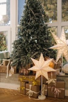 Piękna choinka z prezentami przy dużym oknie. zima nadchodzi. pled z poduszkami