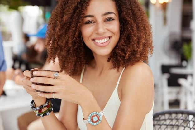 Piękna ciemnoskóra uśmiechnięta kobieta z krzaczastą fryzurą, trzyma filiżankę kawy lub espresso, siedzi przed wnętrzem kawiarni.